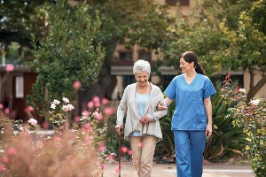 Care professional walking with elderly lady in the garden at a Retirement Home in Peoria IL
